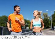 Купить «couple with fitness trackers running along bridge», фото № 30527714, снято 5 июля 2015 г. (c) Syda Productions / Фотобанк Лори