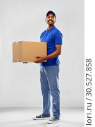 Купить «happy indian delivery man with parcel box in blue», фото № 30527858, снято 12 января 2019 г. (c) Syda Productions / Фотобанк Лори