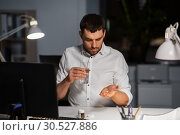 Купить «businessman taking medicine pills at night office», фото № 30527886, снято 25 января 2019 г. (c) Syda Productions / Фотобанк Лори