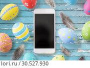 Купить «smartphone with easter eggs and quail feathers», фото № 30527930, снято 15 марта 2018 г. (c) Syda Productions / Фотобанк Лори