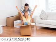 Купить «happy couple having fun with boxes at new home», фото № 30528010, снято 25 февраля 2016 г. (c) Syda Productions / Фотобанк Лори