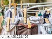 Купить «White and colored linen to be dried on the clothesline with wooden clothespins.», фото № 30528166, снято 2 октября 2018 г. (c) Tetiana Chugunova / Фотобанк Лори