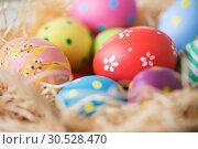 Купить «close up of colored easter eggs in straw», фото № 30528470, снято 15 марта 2018 г. (c) Syda Productions / Фотобанк Лори