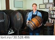 Купить «Man in apron having wood with wine in hands», фото № 30528486, снято 6 июня 2020 г. (c) Яков Филимонов / Фотобанк Лори