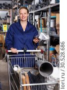 Купить «Smiling female worker in uniform with basket purchasing construction materials», фото № 30528686, снято 20 сентября 2018 г. (c) Яков Филимонов / Фотобанк Лори