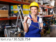 Купить «Young female in uniform and helmet holding saw near shelves with tools», фото № 30528754, снято 20 сентября 2018 г. (c) Яков Филимонов / Фотобанк Лори