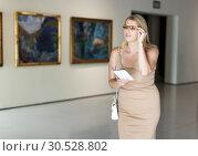 Купить «Woman holding brochure in museum of arts», фото № 30528802, снято 22 сентября 2018 г. (c) Яков Филимонов / Фотобанк Лори