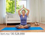 Купить «woman meditating in lotus pose at home», фото № 30528890, снято 13 ноября 2015 г. (c) Syda Productions / Фотобанк Лори