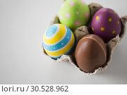 Купить «close up of chocolate and colored easter eggs», фото № 30528962, снято 22 марта 2018 г. (c) Syda Productions / Фотобанк Лори