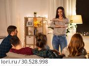 Купить «happy friends playing charades at home in evening», фото № 30528998, снято 22 декабря 2018 г. (c) Syda Productions / Фотобанк Лори