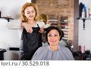 Купить «Hairdresser does to woman haircut with use of scissors and hairbrushes», фото № 30529018, снято 7 марта 2017 г. (c) Яков Филимонов / Фотобанк Лори