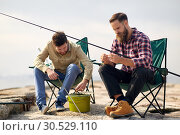 Купить «friends adjusting fishing rods with bait on pier», фото № 30529110, снято 8 сентября 2018 г. (c) Syda Productions / Фотобанк Лори