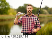 Купить «bearded fisherman with fishing rod and fish catch», фото № 30529114, снято 8 сентября 2018 г. (c) Syda Productions / Фотобанк Лори