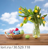 Купить «colored easter eggs in basket and flowers over sky», фото № 30529118, снято 15 марта 2018 г. (c) Syda Productions / Фотобанк Лори