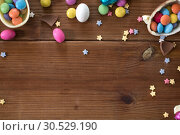 Купить «chocolate eggs and candy drops on wooden table», фото № 30529190, снято 22 марта 2018 г. (c) Syda Productions / Фотобанк Лори