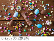 chocolate eggs, easter bunny and candies on wood. Стоковое фото, фотограф Syda Productions / Фотобанк Лори