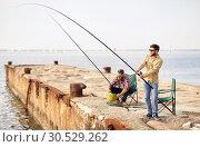 Купить «happy friends with fishing rods on pier», фото № 30529262, снято 8 сентября 2018 г. (c) Syda Productions / Фотобанк Лори