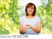 Купить «smiling senior woman with fitness tracker», фото № 30529398, снято 8 февраля 2019 г. (c) Syda Productions / Фотобанк Лори