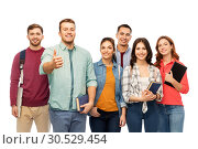 Купить «group of smiling students showing thumbs up», фото № 30529454, снято 10 ноября 2018 г. (c) Syda Productions / Фотобанк Лори