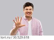 Купить «young man showing five fingers over grey», фото № 30529618, снято 3 февраля 2019 г. (c) Syda Productions / Фотобанк Лори