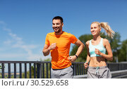 Купить «couple with fitness trackers running along bridge», фото № 30529658, снято 5 июля 2015 г. (c) Syda Productions / Фотобанк Лори