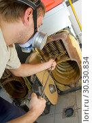 Купить «Repair man servicing big gas boiler», фото № 30530834, снято 11 июня 2010 г. (c) Tryapitsyn Sergiy / Фотобанк Лори