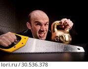 Купить «Man with saw and heavy weight of gold», фото № 30536378, снято 14 февраля 2011 г. (c) Tryapitsyn Sergiy / Фотобанк Лори