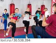 Купить «Sporty women and their trainer are doing kick in gym.», фото № 30538394, снято 8 октября 2017 г. (c) Яков Филимонов / Фотобанк Лори