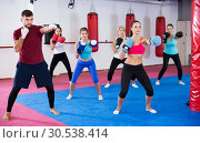Купить «women are boxing and doing kick with coach», фото № 30538414, снято 8 октября 2017 г. (c) Яков Филимонов / Фотобанк Лори