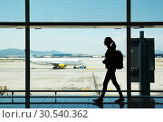 Young woman walking at airport. Стоковое фото, фотограф Tryapitsyn Sergiy / Фотобанк Лори