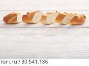 Купить «baguette on white wooden background», фото № 30541186, снято 26 марта 2019 г. (c) Майя Крученкова / Фотобанк Лори