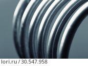 Купить «Aluminum spiral isolated on gray background», фото № 30547958, снято 10 апреля 2014 г. (c) Tryapitsyn Sergiy / Фотобанк Лори