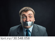 Купить «Man with mouth covered by masking tape», фото № 30548058, снято 21 апреля 2014 г. (c) Tryapitsyn Sergiy / Фотобанк Лори