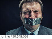 Купить «Man with mouth covered by masking tape», фото № 30548066, снято 21 апреля 2014 г. (c) Tryapitsyn Sergiy / Фотобанк Лори