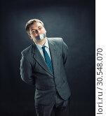 Купить «Man with mouth covered by masking tape», фото № 30548070, снято 21 апреля 2014 г. (c) Tryapitsyn Sergiy / Фотобанк Лори