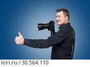 Photographer with digital camera shows thumb up. Стоковое фото, фотограф Tryapitsyn Sergiy / Фотобанк Лори