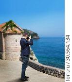 Male photographer taking picture of sea coast. Стоковое фото, фотограф Tryapitsyn Sergiy / Фотобанк Лори