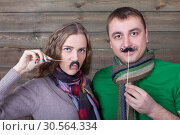 Купить «Cute couple with funny moustache on a sticks», фото № 30564334, снято 22 декабря 2016 г. (c) Tryapitsyn Sergiy / Фотобанк Лори