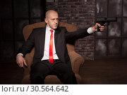 Купить «Bald killer in suit and red tie aims a pistol», фото № 30564642, снято 19 января 2017 г. (c) Tryapitsyn Sergiy / Фотобанк Лори