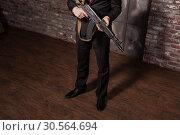 Купить «Assassin in suit and red tie holding machine gun», фото № 30564694, снято 19 января 2017 г. (c) Tryapitsyn Sergiy / Фотобанк Лори