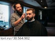 Купить «Barber combing hair of the client in salon cape», фото № 30564902, снято 26 января 2017 г. (c) Tryapitsyn Sergiy / Фотобанк Лори