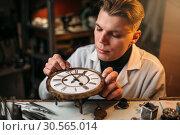 Купить «Watchmaker adjusts the mechanism of old watches», фото № 30565014, снято 28 января 2017 г. (c) Tryapitsyn Sergiy / Фотобанк Лори