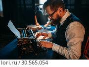 Bearded journalist in glasses typing on typewriter. Стоковое фото, фотограф Tryapitsyn Sergiy / Фотобанк Лори