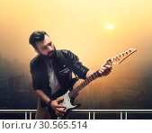 Male brutal solo guitarist with electric guitar. Стоковое фото, фотограф Tryapitsyn Sergiy / Фотобанк Лори