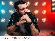 Bearded singer on stage with decorations of lights. Стоковое фото, фотограф Tryapitsyn Sergiy / Фотобанк Лори