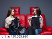 Two women sitting on couch and tries on dresses. Стоковое фото, фотограф Tryapitsyn Sergiy / Фотобанк Лори