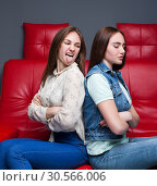 Two quarreling girls sits on red leather couch. Стоковое фото, фотограф Tryapitsyn Sergiy / Фотобанк Лори