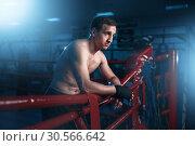 Купить «Boxer in black handwraps poses on ring ropes», фото № 30566642, снято 19 мая 2017 г. (c) Tryapitsyn Sergiy / Фотобанк Лори