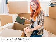 Купить «Smiling girl unpacking cardboard boxes, new home», фото № 30567306, снято 29 июня 2017 г. (c) Tryapitsyn Sergiy / Фотобанк Лори