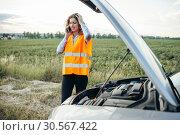 Купить «Girl in reflecting vest with phone, broken car», фото № 30567422, снято 9 июля 2017 г. (c) Tryapitsyn Sergiy / Фотобанк Лори